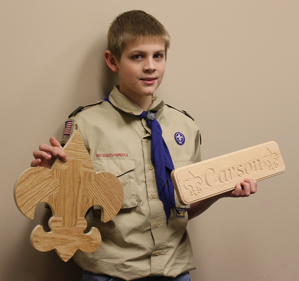 A Scout holding up his emblem puzzle and name plaque