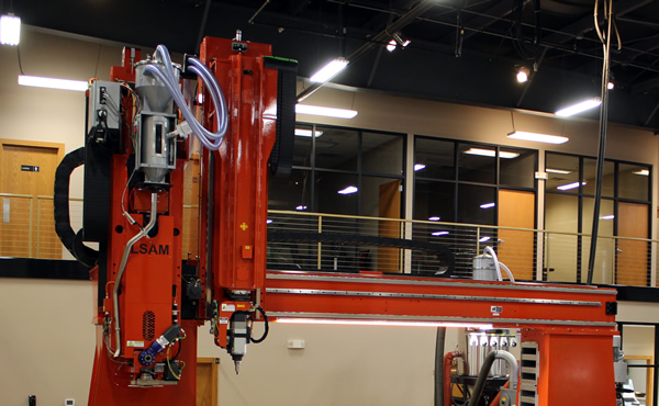 A single moving gantry on the LSAM 1010 carries both the print and trim heads just like on the MT.