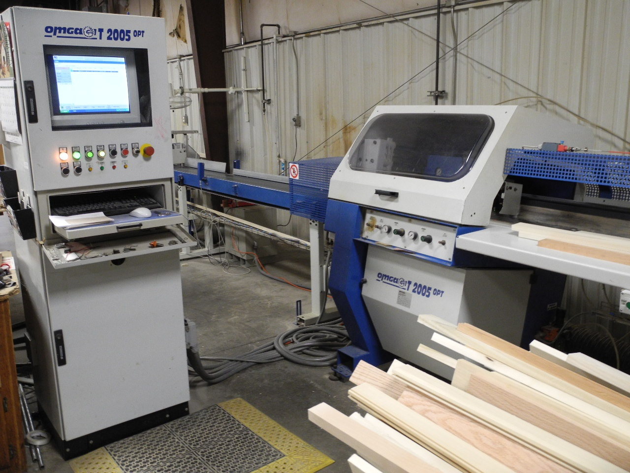 Boards are fed through an Omga GT 2005 OPT cutoff saw and optimizer that cuts pieces of clean lumber.