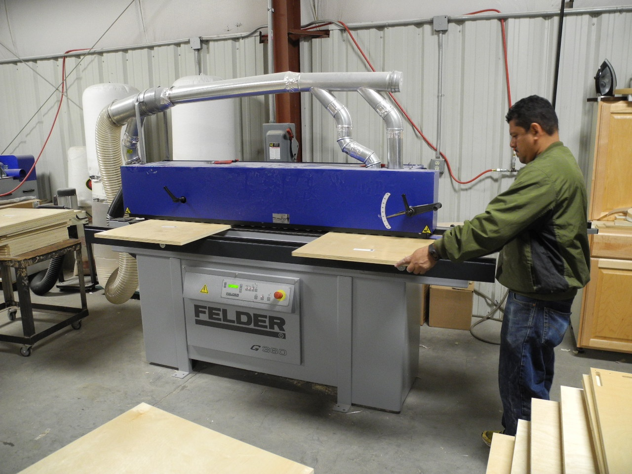 A Felder G360 edgebander is being used to edgeband cabinet parts.